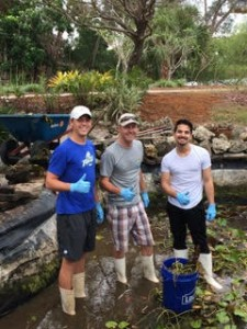 Ross Becker (center) and his team, de-mucking the pond in the Fragrance Garden at Lakes Park | Photo: Karen Miller