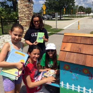 Troop members load books into their creation - the new Little Free Library at the Children's Garden in Lakes Park