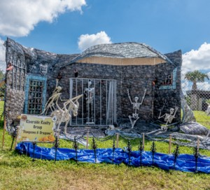 2018 Scarecrows in the Park winner Riverside Realty/Staging Matters. Display depicts a stone dungeon with skeletons of people and creatures being held captive.