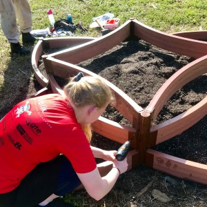 "Katherine works on securing the frame of one of the Lakes Park Children's Garden's ""star beds"""